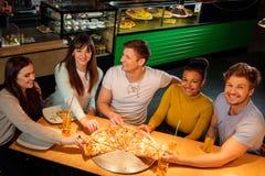 Amis multiraciaux gais ayant l'amusement mangeant dans la pizzeria Image libre de droits
