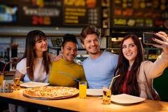 Amis multiraciaux gais prenant le selfie dans la pizzeria Image libre de droits