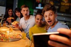 Amis multiraciaux gais prenant le selfie dans la pizzeria Photos stock