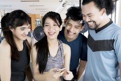 Amis multiraciaux heureux à l'aide d'un smartphone Images libres de droits