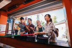 Amis multiraciaux jouant le jeu électronique au parc d'attractions Image libre de droits