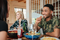 Amis multiraciaux mangeant, buvant et parlant à la maison la table Photos stock