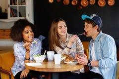 Amis multiraciaux mangeant dans un café Images libres de droits