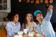 Amis multiraciaux mangeant dans un café Photographie stock