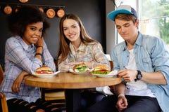 Amis multiraciaux mangeant dans un café Images stock