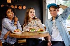 Amis multiraciaux mangeant dans un café Image stock