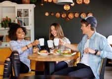 Amis multiraciaux mangeant dans un café Photographie stock libre de droits
