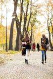 Amis multiraciaux marchant en parc d'automne Photographie stock libre de droits