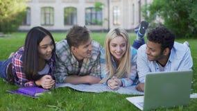 Amis multiraciaux observant et discutant la vidéo drôle sur l'ordinateur portable, étudiants clips vidéos