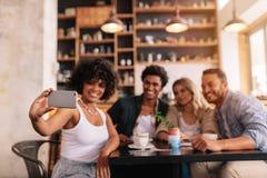 Amis multiraciaux prenant le selfie au téléphone intelligent au café Photographie stock libre de droits
