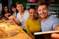 Amis multiraciaux prenant le selfie dans la pizzeria Image libre de droits