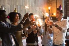 Amis multiraciaux tenant des verres de cierges magiques, célébrant le toget Photographie stock libre de droits