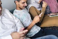 Amis musulmans employant le media social aux téléphones Photographie stock