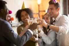 Amis noirs et blancs heureux faisant tinter des verres célébrant la partie Photos stock