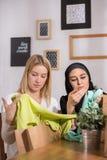 Amis observant de nouveaux vêtements Photographie stock