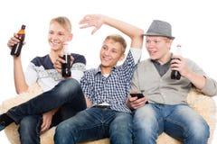 Amis observant des programmes à la TV Images libres de droits