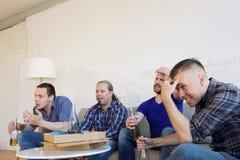 Amis observant desserrant le match de football Photo libre de droits