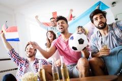 Amis observant la partie de football à la maison Image libre de droits