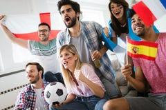 Amis observant la partie de football à la maison Photo stock