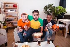 Amis observant la partie de football Photos stock
