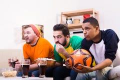 Amis observant la partie de football Photographie stock