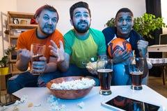 Amis observant la partie de football Photographie stock libre de droits