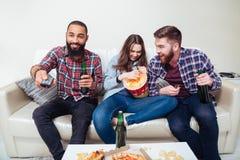 Amis observant la TV à la maison et rire Photo libre de droits
