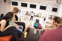 Amis observant le bowling de femme dans l'allée Images libres de droits