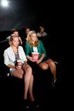 Amis observant le film au cinéma Image stock