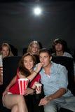 Amis observant le film au cinéma Images stock