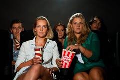 Amis observant le film au cinéma Image libre de droits