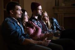 Amis observant le film avec le maïs éclaté à la maison Images libres de droits