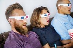 Amis observant le film 3D ensemble Photos stock