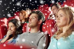 Amis observant le film d'horreur dans le théâtre Photo stock