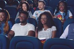 Amis observant le film dans le hall moderne de cinéma Images stock