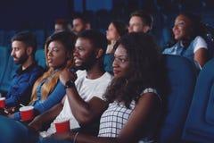 Amis observant le film dans le hall moderne de cinéma Photo stock