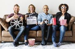 Amis observant le film ensemble à la maison Images libres de droits
