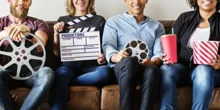 Amis observant le film ensemble sur le divan Image libre de droits
