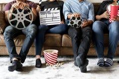 Amis observant le film ensemble sur le divan Images libres de droits