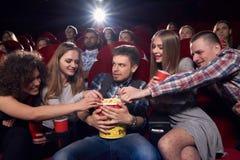 Amis observant le film et tirant la main au maïs éclaté Photos stock