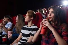 Amis observant le film intéressant au grand hall de cinéma Images stock