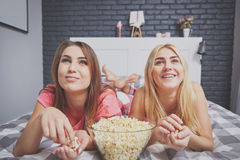Amis observant le film intéressant dans la chambre à coucher Photographie stock