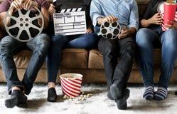 Amis observant le film se reposer ensemble sur le divan Photos stock