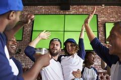 Amis observant le jeu dans la barre de sports sur la célébration d'écrans Image libre de droits