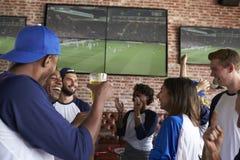 Amis observant le jeu dans la barre de sports sur la célébration d'écrans Photo stock