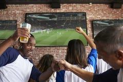 Amis observant le jeu dans la barre de sports sur la célébration d'écrans Photographie stock