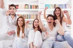 Amis observant le jeu sur encourager de TV Photographie stock