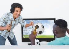 Amis observant le match de football à la télévision tout en ayant la bière Photographie stock