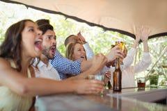 Amis observant le match de football au compteur dans le restaurant Images libres de droits