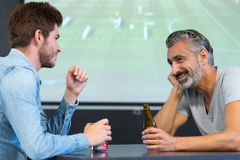 Amis observant le match de football tout en buvant de la bière Image libre de droits